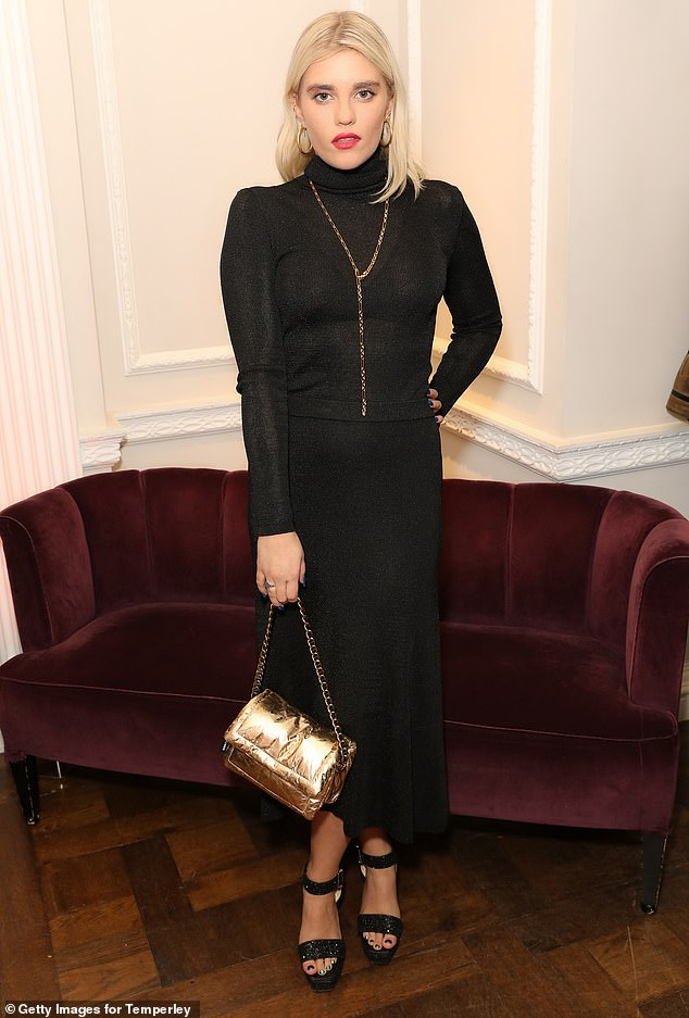 Stunning:Tiger Lilly Taylor, 25, opted for a black fitted polo neck dress. She paired this with a bright red pout and carried a gold bag