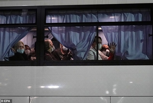 US citizens wave from a bus as they leave the Diamond Princess cruise ship docked at Daikoku Pier Cruise