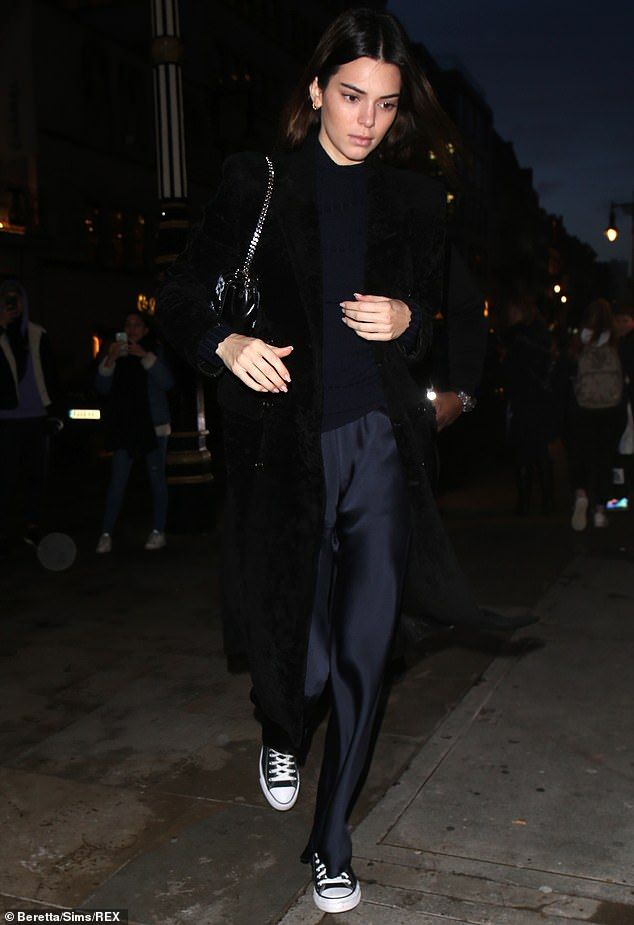 Black Balenciaga: She kept warm in a long black velvet Balenciaga overcoat, which she paired with a ribbed midnight blue turtleneck sweater