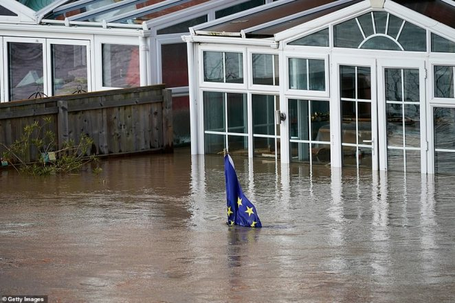 An EU flag in a garden in Hereford is pictured almost completely underwater after the River Wye reached record-breaking levels on Monday