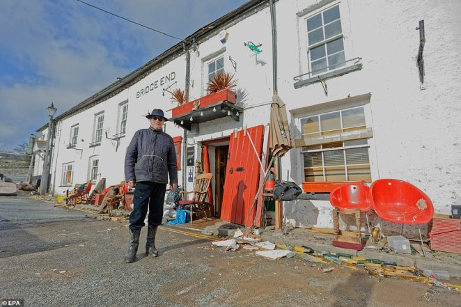 Pub owner Howard Baker stands outside his flood-hit pub, the Bridge End Inn in Crickhowell, Powys, Wales, one of the worst -hit areas in the UK