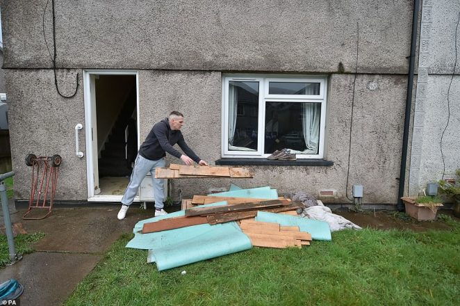 Lee Griffiths throwing out laminate flooring after flooding damaged his house in Nantgarw, South Wales