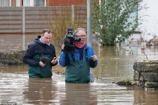 A camera crew wade through the flooded waters after the River Wye burst its banks in Hereford