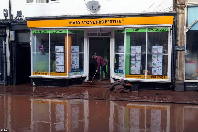 A woman brushes water away from the Mary Stone Properties shopfront, which has been damaged by flood water, in Tenbury Wells, Worcestershire, on Monday