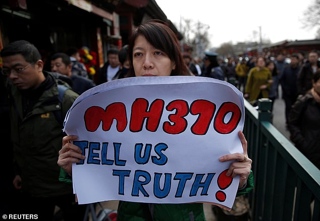 Catherine Gang, whose husband Li Zhi was on board the missing Malaysia Airlines flight MH370, holds a banner as she walks outside the Yonghegong Lama Temple on March 8, 2015 after a gathering of family members of the missing passengers in Beijing
