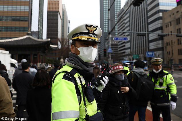 In Seoul, thousands of people took to the streets for a political rally, despite the city's mayor saying the gatherings would be banned (pictured, a police officer wearing a mask)