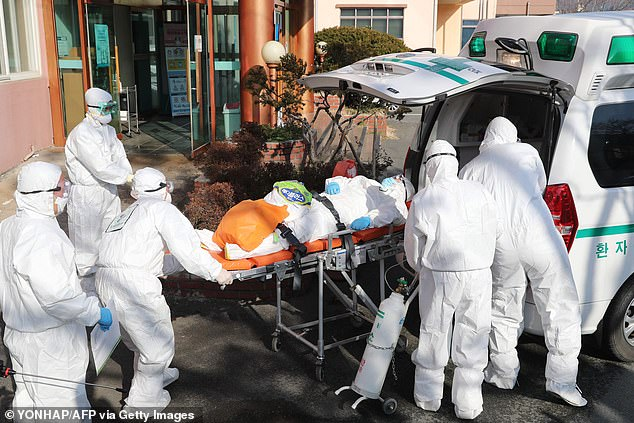 South Korean officials have confirmed reports of outbreaks in the psychiatric unit of a hospital in Cheongdo (pictured, medical workers moving a suspected coronavirus patient)