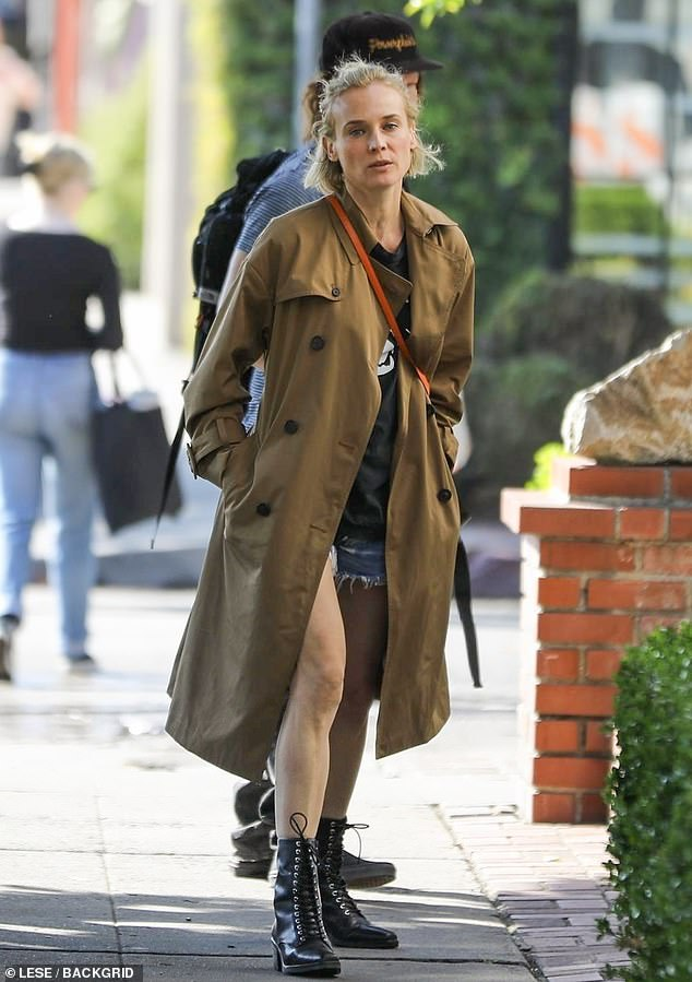 Towering: The 5ft7in Inglourious Basterds star elevated her stature with black boots, and she blocked the breeze with a tan trench coat
