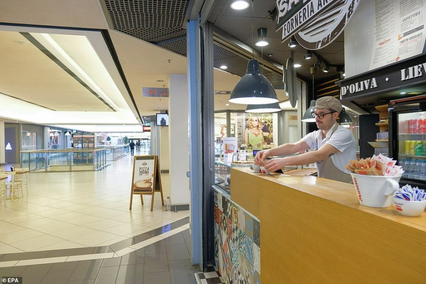 A cafe worker arranges sugar packets inside a shopping mall in Milan, which has been left almost-deserted after the city found itself at the centre of the latest coronavirus outbreak