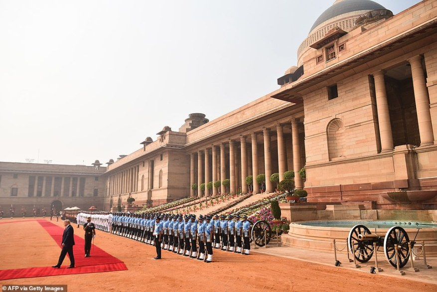 President Trump turns after reviewing a long line of Indian troops in baby blue, white and green