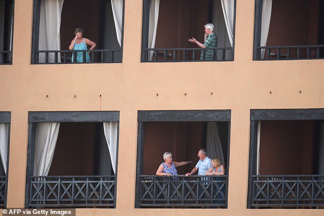 Holidaymakers stand on their balconies, some of them speaking on their phones, as they wait for news during today's lockdown