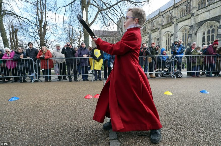 And outside Winchester Cathedral, in Hampshire, a young chorister in full regalia wielded his frying pan as older spectators watched on with delight