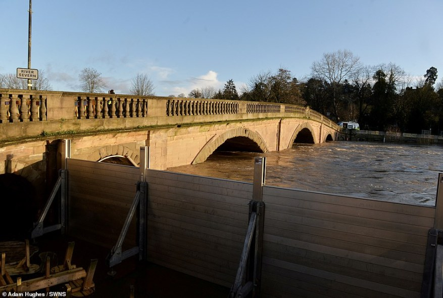 A bridge over the swollen River Severn, in Bewdley, Worcestershire, today is pictured next to the flood defences