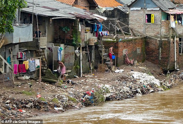 Residents clean up flood damage by the side of a polluted river in Jakarta today, a day after 3ft floods in Indonesia's capital