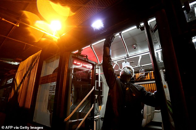A Tehran Municipality worker cleans a bus today with the Iranian regime on the back foot over the growing coronavirus crisis