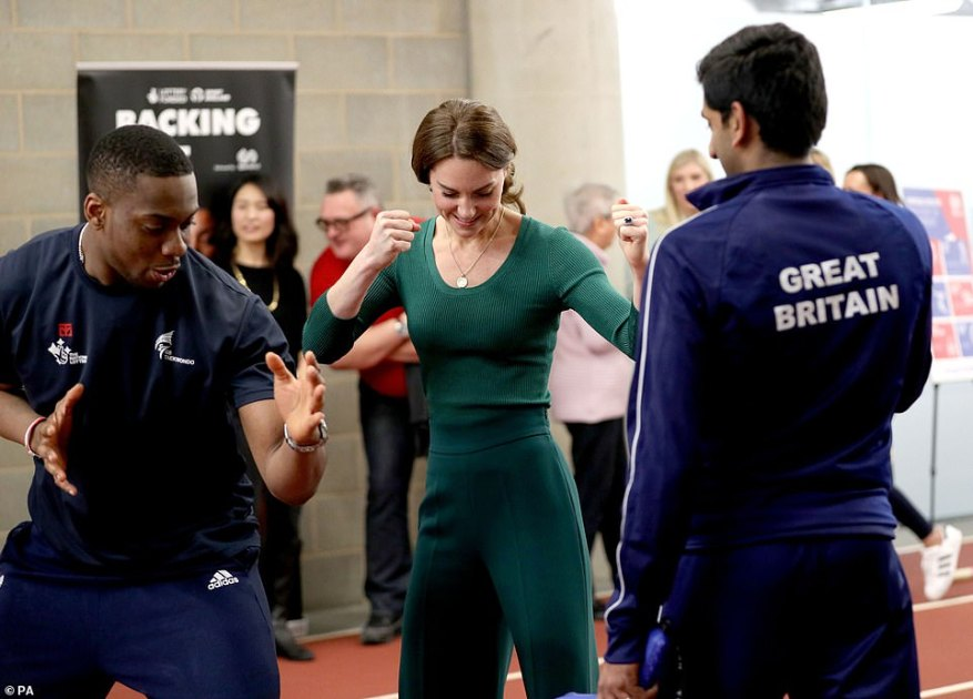 Getting the stance right:The Duchess of Cambridge is shown Taekwondo moves by Lutalo Muhammad, left, at the event