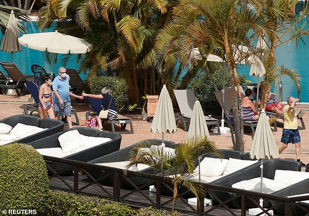 Guests wearing masks lie on sun loungers and walk by the poolside at the Tenerife hotel today