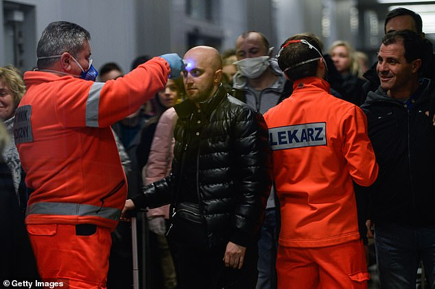 A health worker screens the temperature of a passenger arriving from Milan Bergamo to Krakow International Airport on February 26