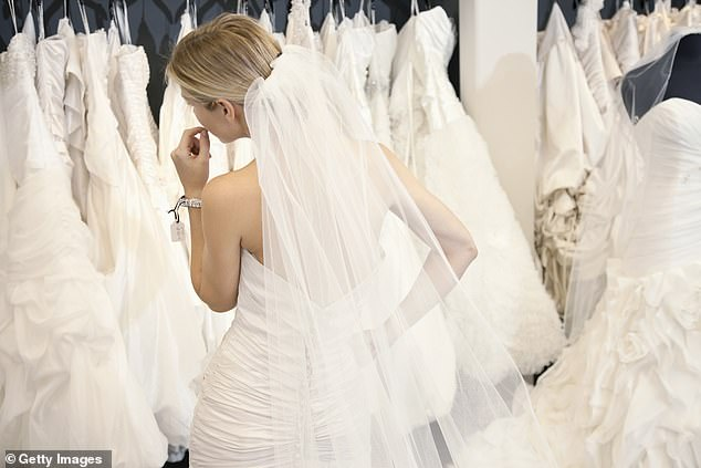 Many dresses sold in Britain come from China and bridal stores 'have found it really difficult because the factories have been closed' (stock image of woman in a dress shop)