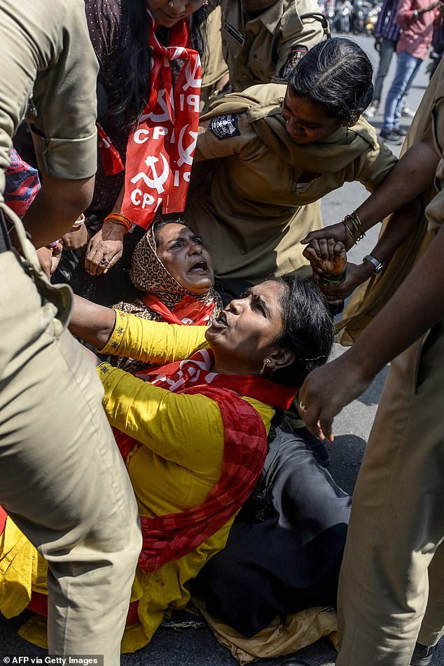 Police personnel detain members of Communist Party of India (CPI) as they demand the resignation of Union Home Minister Amit Shah for the responsibility about the violence in Delhi, during a protest in Hyderabad today