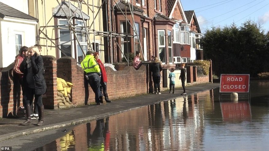 People survey flooding in Snaith, East Yorkshire, today where locals have criticised the lack of help they have received