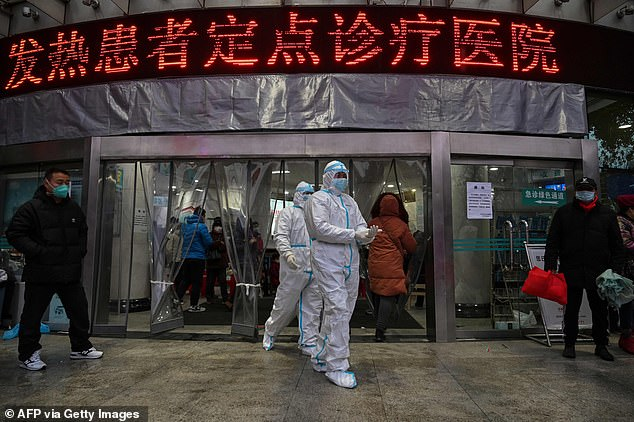 Medical staff members wearing protective clothing to help stop the spread of a deadly virus which began in the city, walk at the Wuhan Red Cross Hospital in China