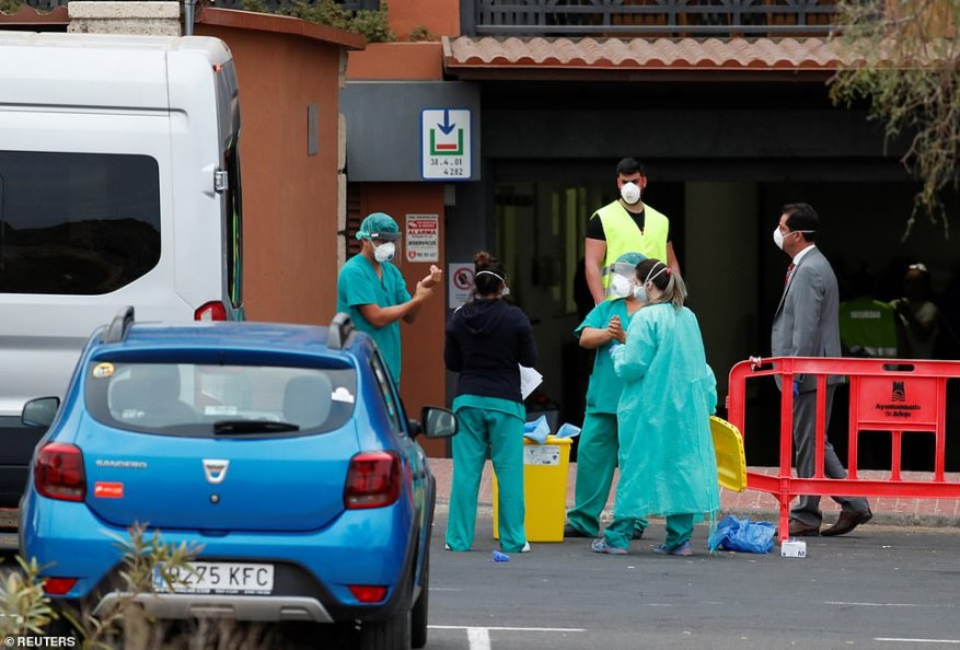 Medical staff prepare to check guests leaving the H10 Costa Adeje Palace today