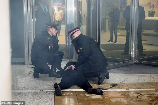 Two officers held down one of the activists outside the London Stock Exchange on Friday