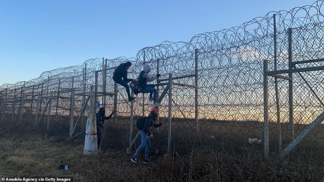 Migrants climb barbed-wire on Turkey's border with Greece in Edirne, Turkey on February 28. Near the Pazarkule border crossing with Greece, Turkish police stopped some 150 refugees about half a mile from the border, preventing them from going further