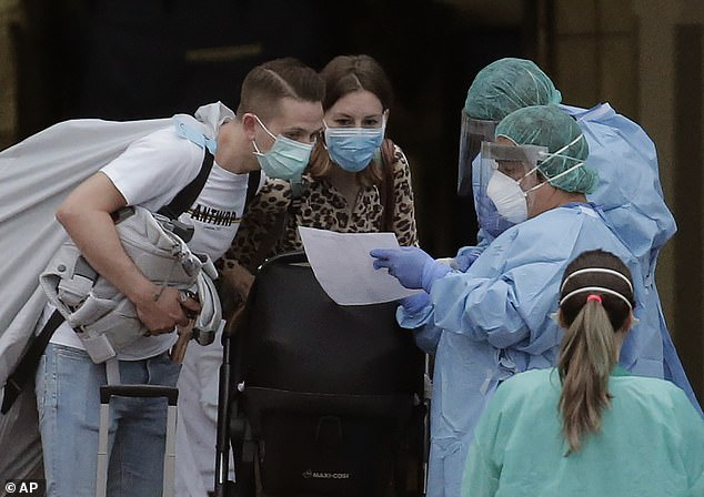 Papers: Staff in protective gear assist guests as they leave the Tenerife hotel.A total of 130 guests from 11 countries have been told they can leave the hotel after undergoing screening because they arrived after those who tested positive had been taken to hospital