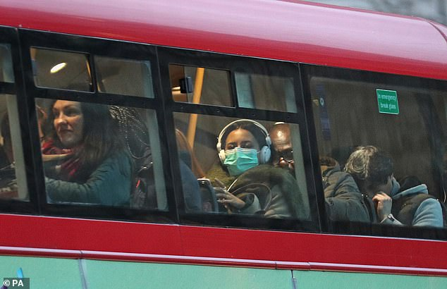 A woman wearing a face mask on a bus in London, where the UK's 20th case is being treated