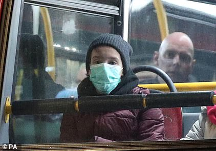 A bus passenger wears a protective mask in London