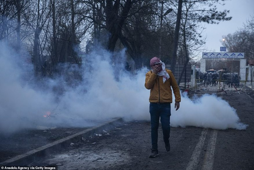 A man covers his face after Greek police shot tear gas at migrants on the Greece-Turkey border earlier today