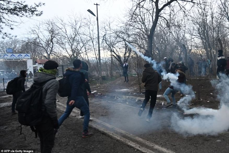 A migrant throws back a tear gas canister toward Greek anti-riot police officers on the buffer zone Turkey-Greece border, at Pazarkule, in Edirne district today