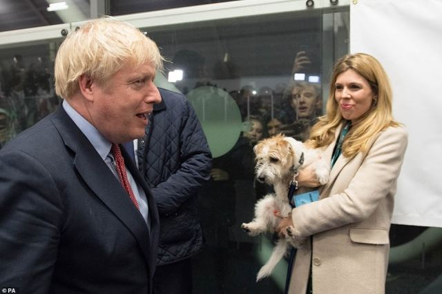 A proud Ms Symonds looks on with pet dog Dilyn shortly after Boris Johnson's resounding general election victory in December