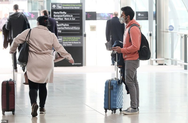 Just 48 hours ago, the first case in Northern Ireland was made public - as it's revealed more than 10,000 Britons have now been tested for the deadly virus. Pictured: A man wearing a facemask in Dublin Airport