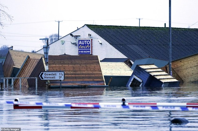 Storm Jorge has swept into the UK bringing four inches of rain, fierce winds and snow as drivers are urged to avoid unnecessary travel. Pictured: Garden sheds floating in the flood water in Snaith as dozens of homes and businesses were hit by Storm Jorge