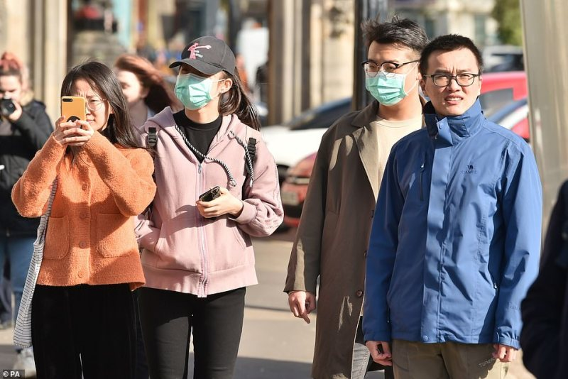 Pictured: People wearing face masks ahead of the St David's Day Parade in Cardiff today as fears continue to sweep Britain while the coronavirus crisis unfolds