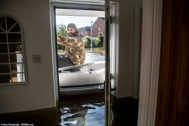 Dave Towers, 38, helps move belongings from homes on the heavily flooded George Street in Snaith, East Yorkshire on Sunday