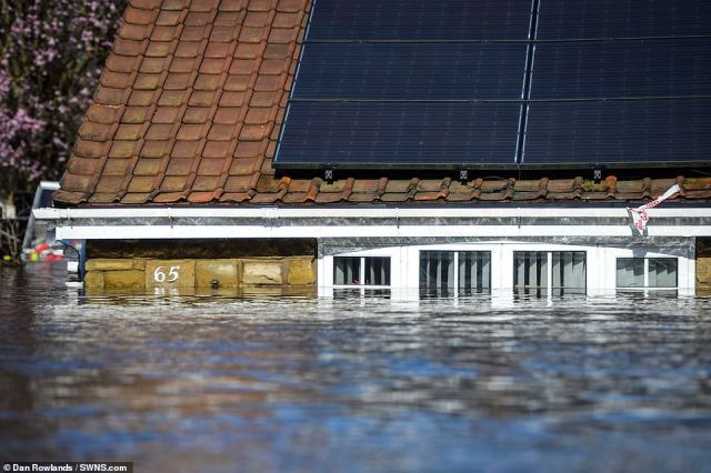 Heartbreaking photographs from outside their home show it almost entirely underwater, with just its roof and solar panels protruding from the water's surface
