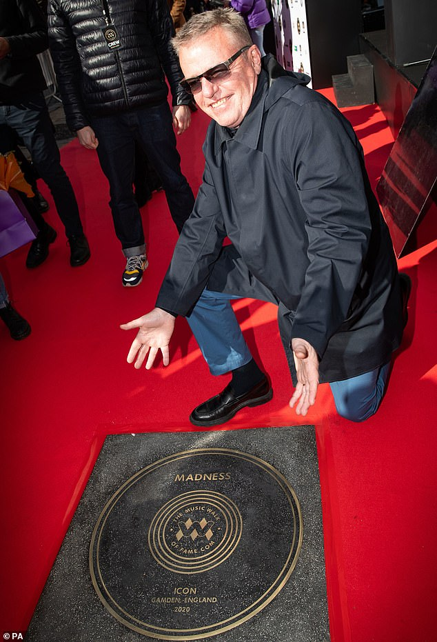 Music maker: Suggs beamed as he kneeled down beside the band's slab, which is close to music venue Electric Ballroom nightclub on Camden High Street