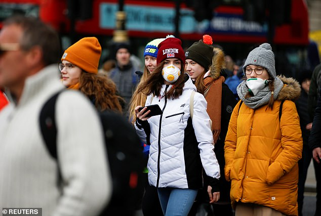 Pedestrians in central London wearing face masks this afternoon as the economic impact of the outbreak worsened