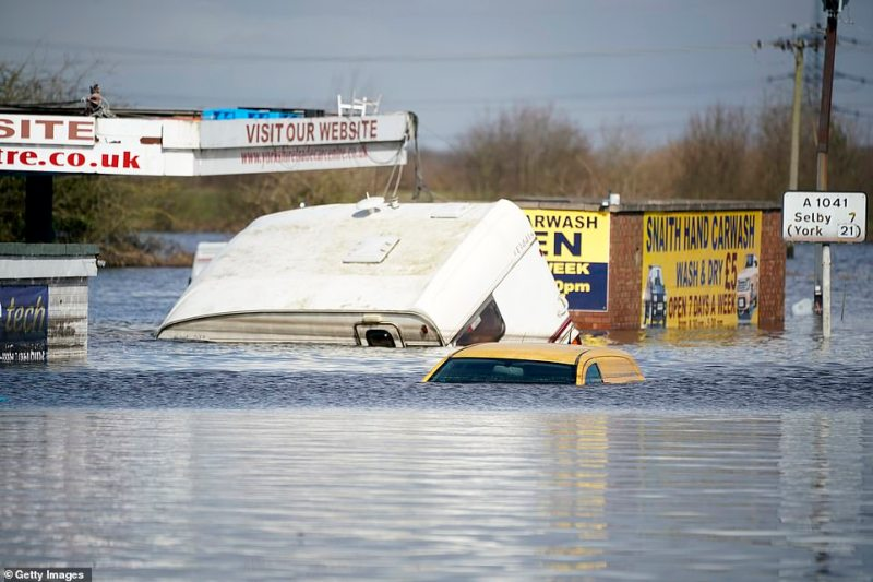 A caravan and a small van, seen today, are among the vehicles swallowed up the floodwater in the village of Snaith, near the River Aire