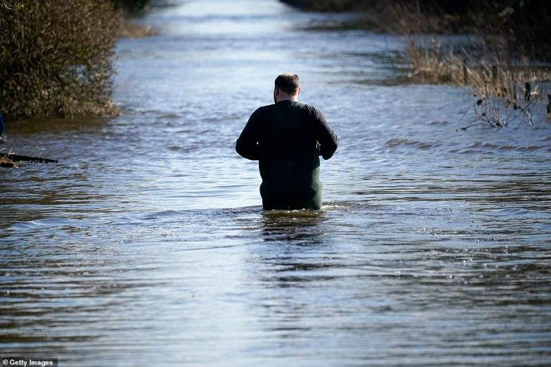 A man walks through waist-high water today in the village of East Cowick to survey the damage caused by floodwater last week
