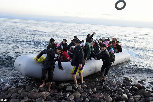 Migrants lift their inflatable boat onto the shore at the village ofSkala Sikaminias, on the Greek island of Lesbos, after crossing on a dinghy from Turkey today