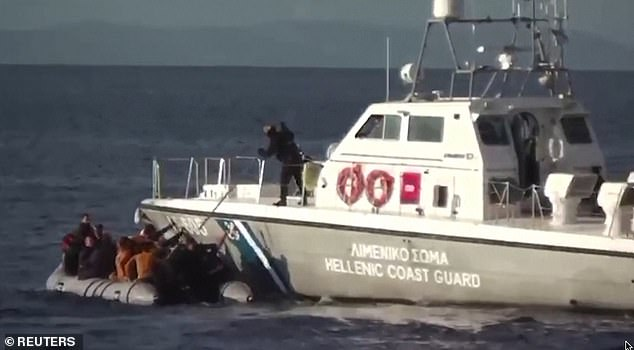 Another clip shows migrants trying to reach for help at the side of the large vessel while a coast guard uses a stick to push them and their boat away