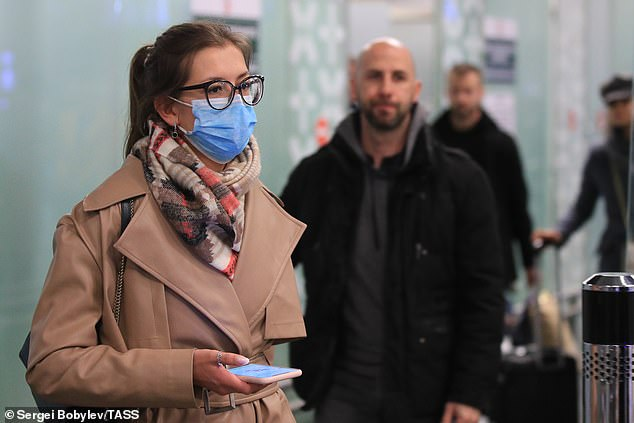 Budget airline Ryanair is to cut flights in and out of Italy, its largest market, by 25 per cent for three weeks. Pictured: A passenger wears a mask in arriving from Italy at Vnukovo International Airport, Russia