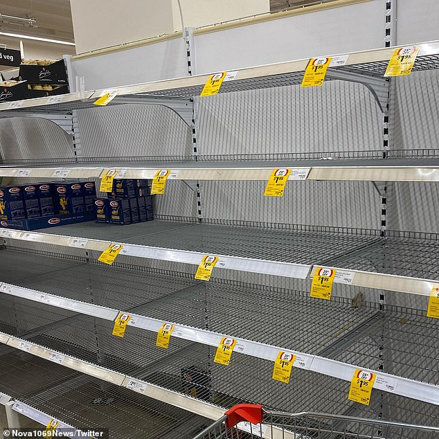 Supermarket shelves have been stripped bare as shoppers race to pile up on food (Pictured: Brisbane Woolworths with pasta shelves entirely empty)