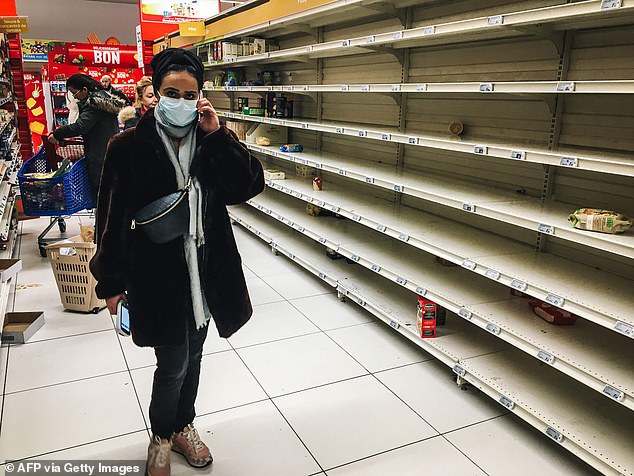 A woman with a face mask stands near empty stalls in a supermarket in the Qwartz shopping centre in Villeneuve-la-Garenne, north of Paris, on March 2, 2020. - Supermarket shelves in countries affected by the COVID-19 virus have been emptied of basic necessities, such as pasta and toilet paper, in recent days but there is no shortage so far
