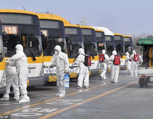 Working from home will be mandatory for employees at the company's South Korea, Hong Kong and Japan offices. Pictured: workers wearing protective gear spray disinfectant as a precaution against coronavirus at a bus station in Gwangju, South Korea today
